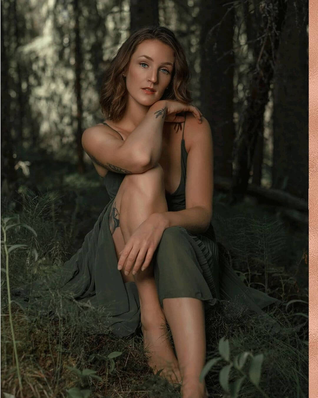 Beautiful inked Canadian model Robyn LS @robin.in.the.clouds sitting on the ground bare foot in the woods showing her sexy calves wearing a green dress for a boudoir photo session by Kelvin Vinx Comendador @vinxreddervon