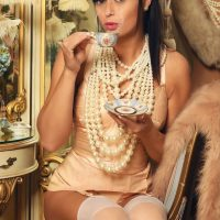 Beautiful American model Lil Mizz Unique @lilmizzunique wearing peach lingerie with pearls drinking tea in a vintage boudoir session