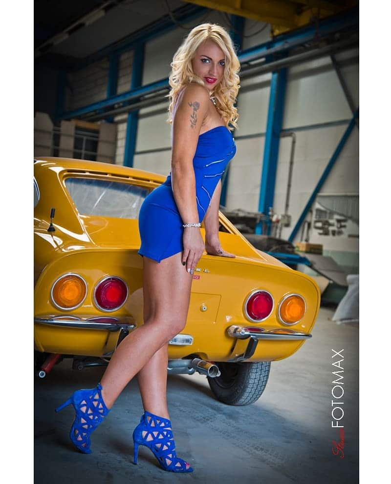 Beautiful Dutch blonde model Willeke Bartels @willekebartels.fitmodel wearing a tight blue dress and high heels showing some toned legs and fit body in front of a yellow Opel GT. Photo by Max Bredschneyder @maxbredschneyder