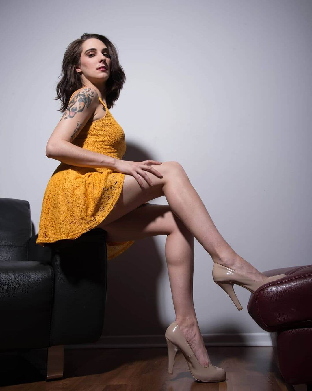 Beautiful Canadian inked model Ashley Stevens @ashley.s.modeling wearing a light orange dress and high heels shot from below showing an upstart view of her long sexy legs
