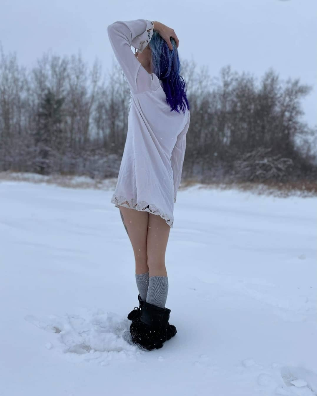 Beautiful Canadian goth snow queen Tora Reign @tora_reign shot from the back holding one arm up showing her sexy thighs and silhouette doing a sensual outdoor photoshoot