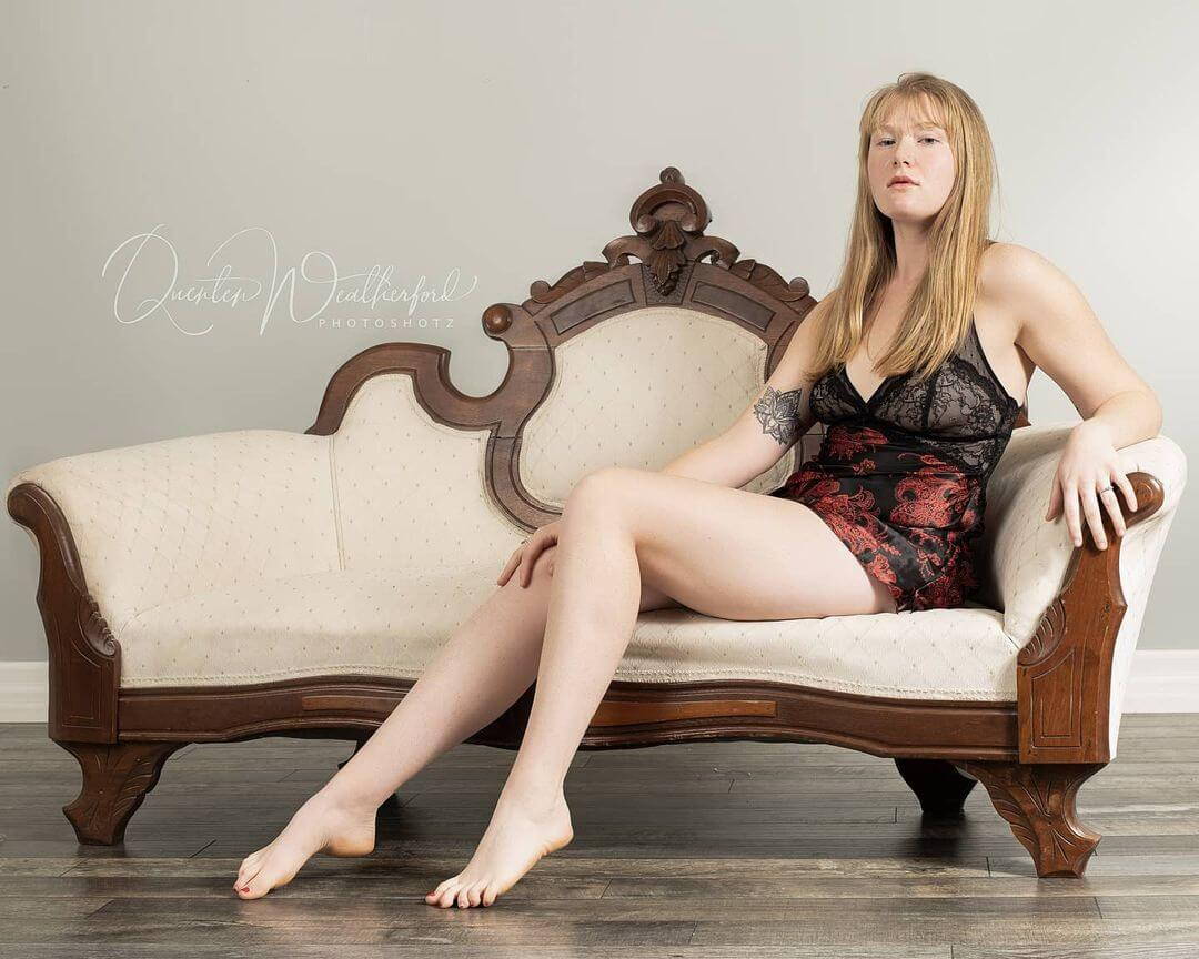 Beautiful Canadian red head model Sarah Samantha @sarah_samantha wearing black lingerie sitting barefoot showing off her long bare legs in a boudoir photo session