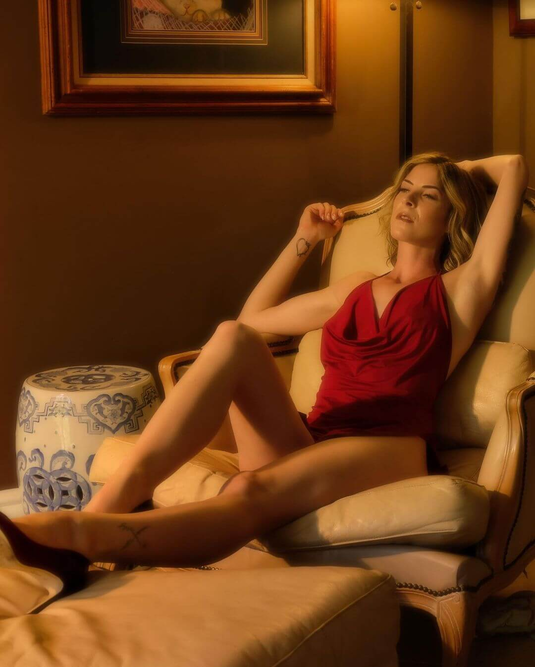 Beautiful American model Cherish @cherishthemodel sitting on a leather chair wearing a red dress and black high heels putting her long sexy legs on display in a sensual photo session