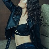 Beautiful actress and model Devi Giannetti wearing black lingerie and a leather jacket