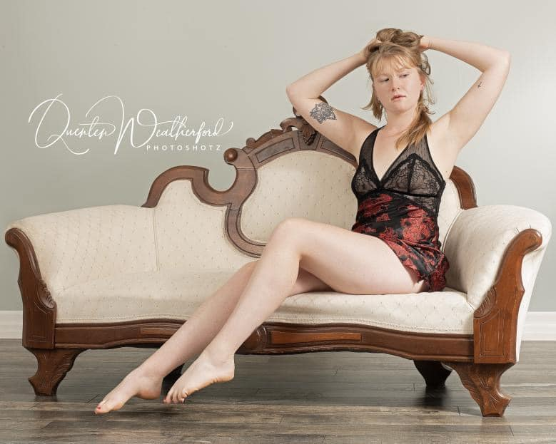 Beautiful Canadian red head model Sarah Samantha @sarah_samanthasitting bare feet with her arms up wearing black lingerie showing her sexy legs in a boudoir photo session
