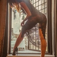 Sensual woman wearing transparent black lace lingerie and high heels