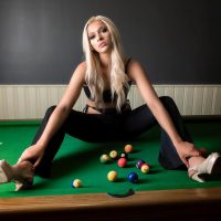 Beautiful blonde model sitting on a pool table wearing high heels holding her feet