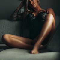 Beautiful blonde inked model Hayden @hayden0586 sitting with her sexy legs open wearing black lingerie in a boudoir session