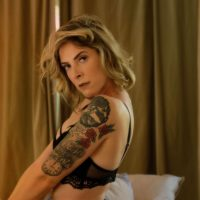 Beautiful inked blonde model wearing black lingerie in a boudoir photo session