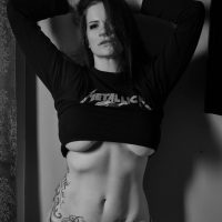 Beautiful rocker model from montreal canada Black Betty @kinky.unikorn wearing a Metallica sweater and denim holding her arms up showing some under boobs and hot fit inked body for a sexy portrait