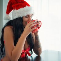 Beautiful tattooed model Msk Black @m.s.k.black drinking a cup of hot coco with her green xmas nails showing some cleavage in a sexy Christmas photo session