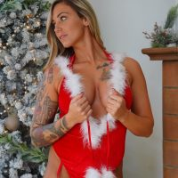 Beautiful inked American model and ex US Army Hayden @hayden0586 wearing a sexy Santa outfit standing in front of a Christmas tree showing her fit tan body and sexy cleavage