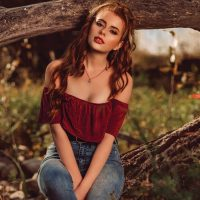 Beautiful model Sara Donnelly @s.aradonnelly wearing a burgundy top and denim jeans sitting on a tree with her hands between her legs for a fall photo session for EVON Magazine by Kelvin Vinx Comendador @vinxreddervon