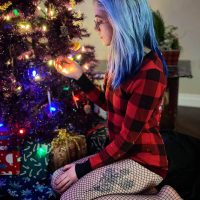 Beautiful pastel goth girl wearing fishnets and a red checkered shirt in front of a Christmas tree