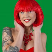 Beautiful blue eyed smiling inked woman with red short hair pinup style