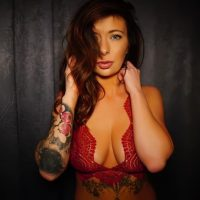 Beautiful blue eyed inked model wearing red lingerie in a sensual portrait session