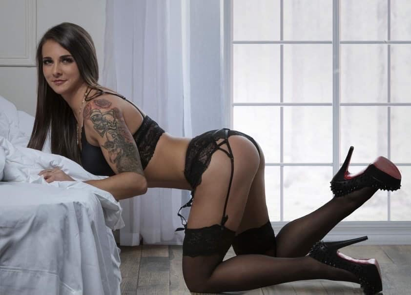 Beautiful Inked Canadian model Djesse B Houle @djessebhoulefitness wearing sexy black lingerie with black stockings and high heels smiling kneeled in front of a bed
