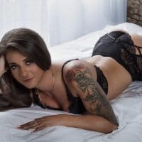 Beautiful Inked model wearing sexy black lingerie with black stockings and high heels
