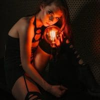 Beautiful young model wearing ripped short black dress and stockings in a dark boudoir ambiance