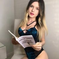 Beautiful Italian model wearing black and blue lingerie reading a book