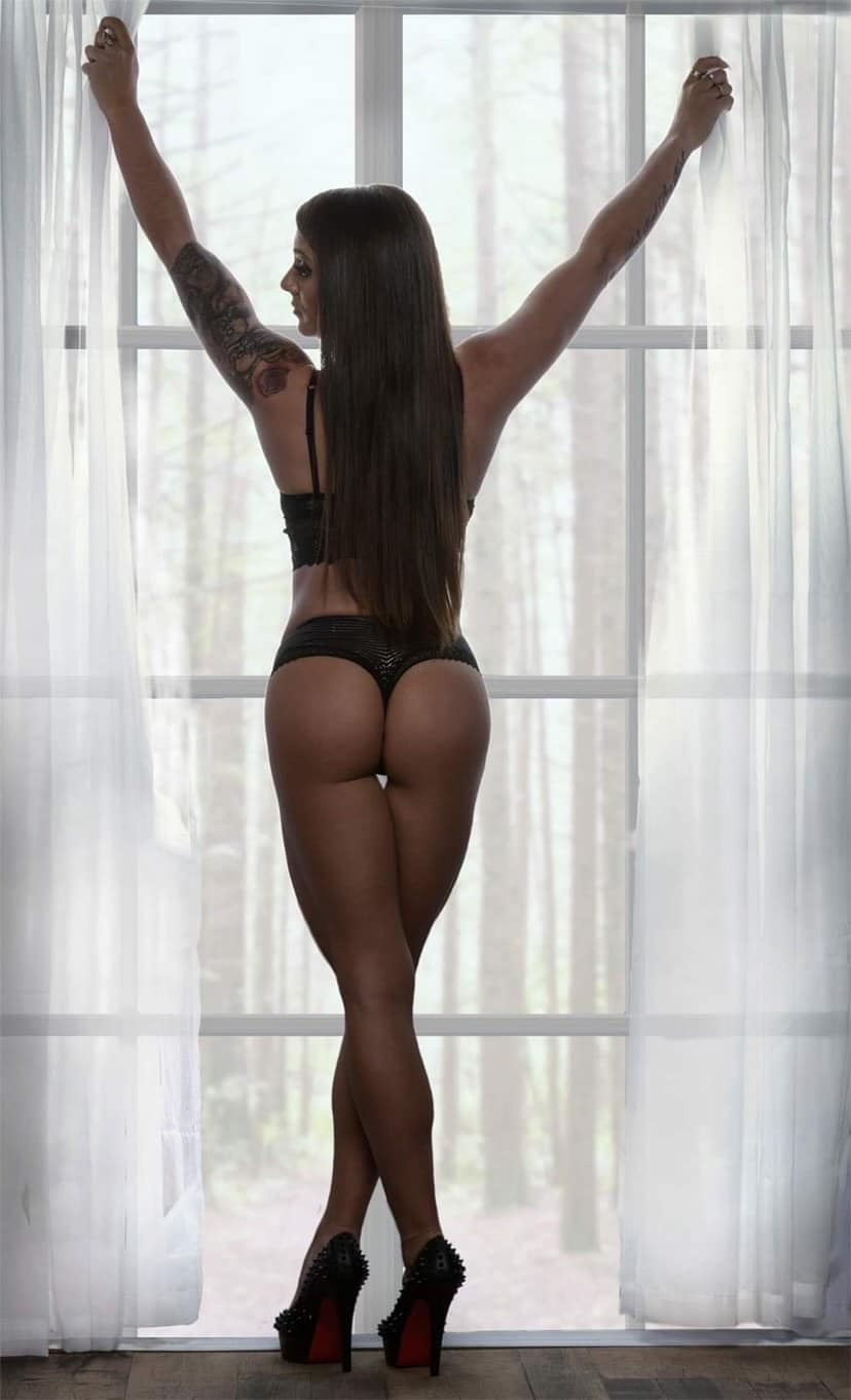 Beautiful Inked Canadian model Djesse B Houle @djessebhoulefitness wearing sexy black lingerie and high heels standing in front of a window showing round ass and her long sexy legs holding both arms up
