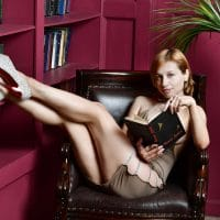 Beautiful Russian model and artist reading a book wearing a short dress showing her legs in high heels