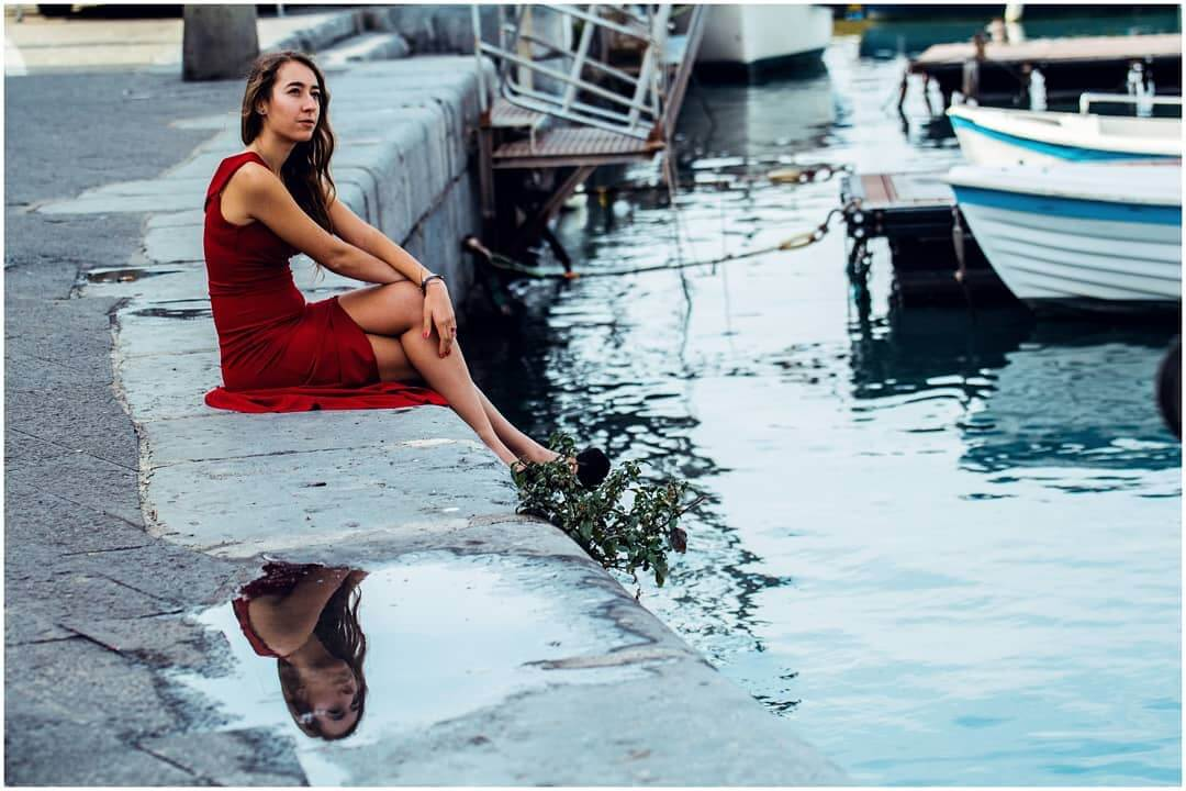 Beautiful Italian model Elisa Ravasio @eli.ravasio_rapcat wearing a long classy red dress sitting by the water with her long sexy legs crossed at the city port