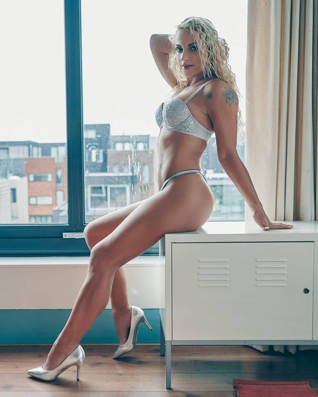 Beautiful blonde Dutch over 30 model and mom Willeke Bartels @willekebartels.fitmodel sitting by the window holding her arm up showing her hot inked body and long sexy legs wearing silver lingerie and high heels in a boudoir photo session