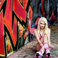 Beautiful blonde German model Michaela Fame Style @modelmichaelafamestyle sitting on the ground with her legs crossed tying and roller skates in an 80's style photo session