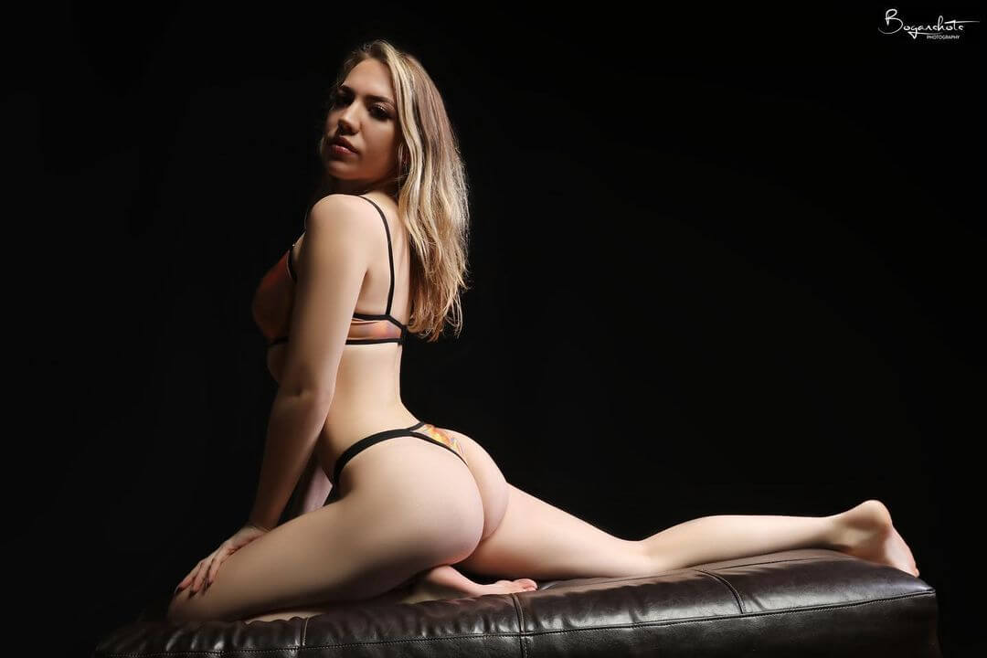 Beautiful Boston blonde model Kaitlin @that.pink.girl_ wearing lingerie kneeling bare feet with her sexy legs spread showing her hot ass posing for a boudoir photo session