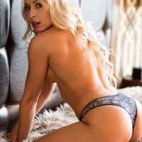 Beautiful blonde model Nicole Alexandra @blondebombshell_model only wearing black panties kneeled on a fur rug showing her sexy beach body while putting out her hot booty in a boudoir photo shoot
