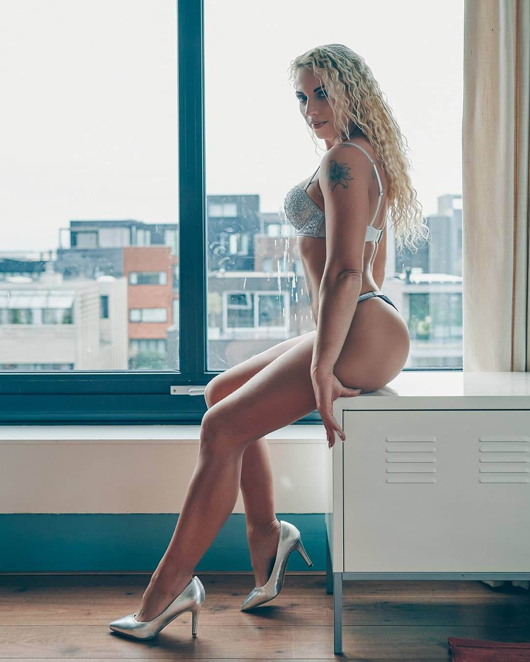 Beautiful blonde Dutch over 30 fit model Willeke Bartels @willekebartels.fitmodel sitting by the window showing her hot tanned body and long sexy legs wearing silver lingerie and high heels in a boudoir photo session