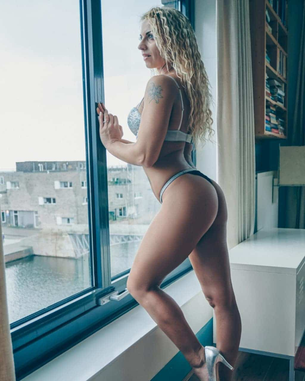 Beautiful blonde Dutch over 30 model and mom Willeke Bartels @willekebartels.fitmodel standing by the window looking away showing her hot inked body and long sexy legs wearing silver lingerie in a boudoir photo session