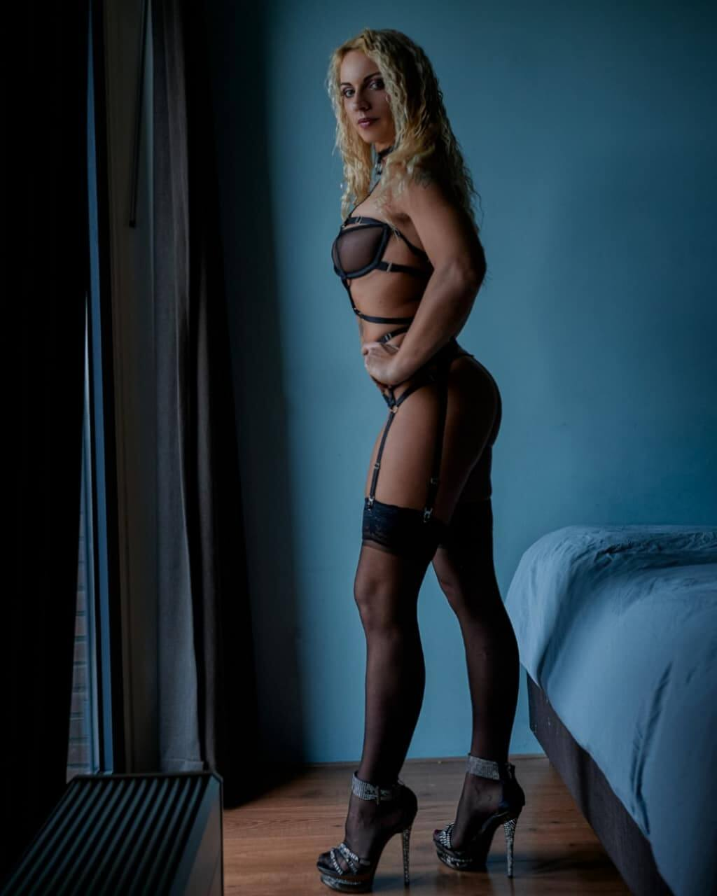 Beautiful blonde Dutch model Willeke Bartels standing in her room showing her sexy body and long hot legs wearing black lingerie with black nylon stockings and high heels in a sensual photo session