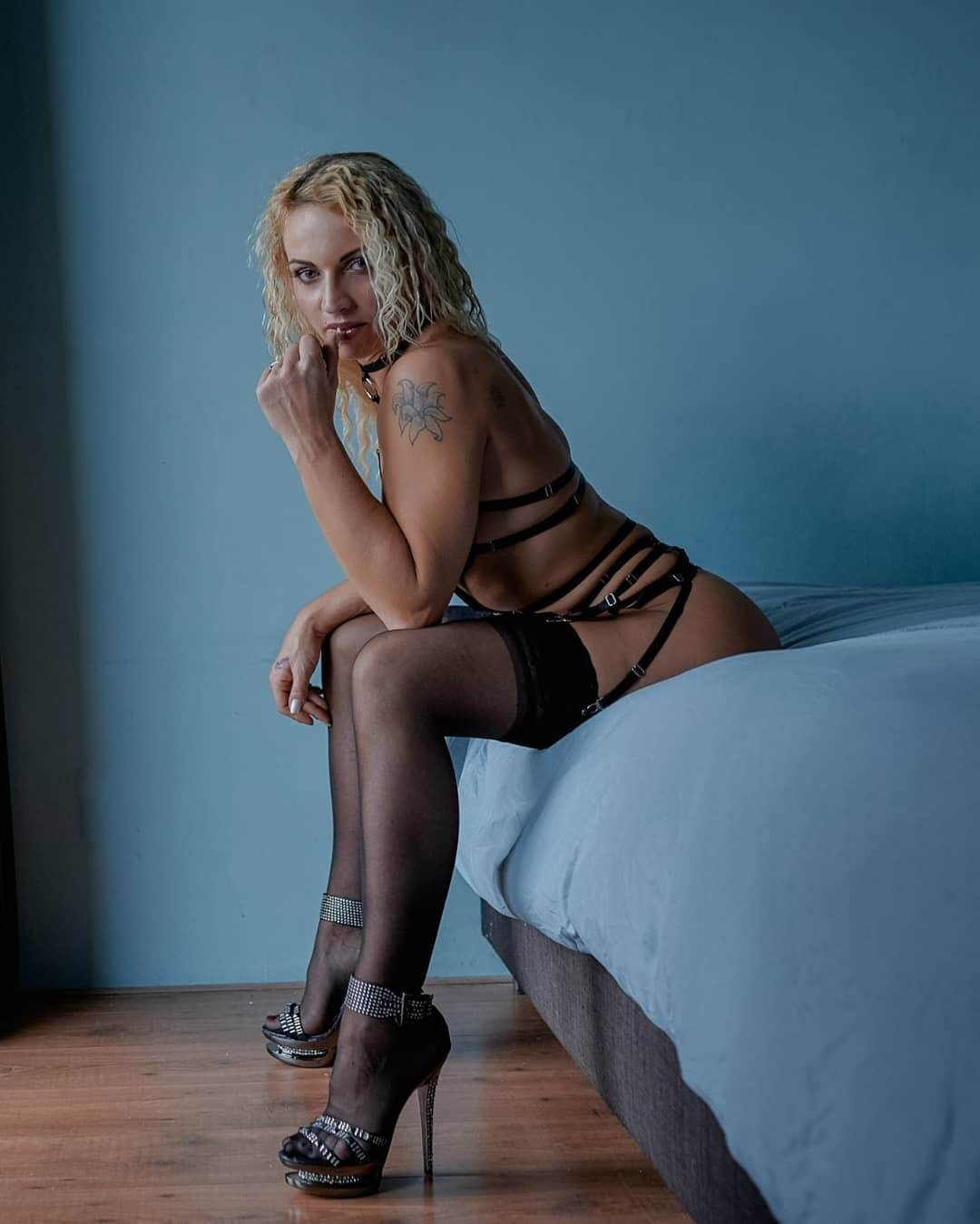 Beautiful blonde Dutch model Willeke Bartels sitting on her bed showing her sexy legs and hot milf body wearing black lingerie with black nylon stockings and high heels in a sensual photo session