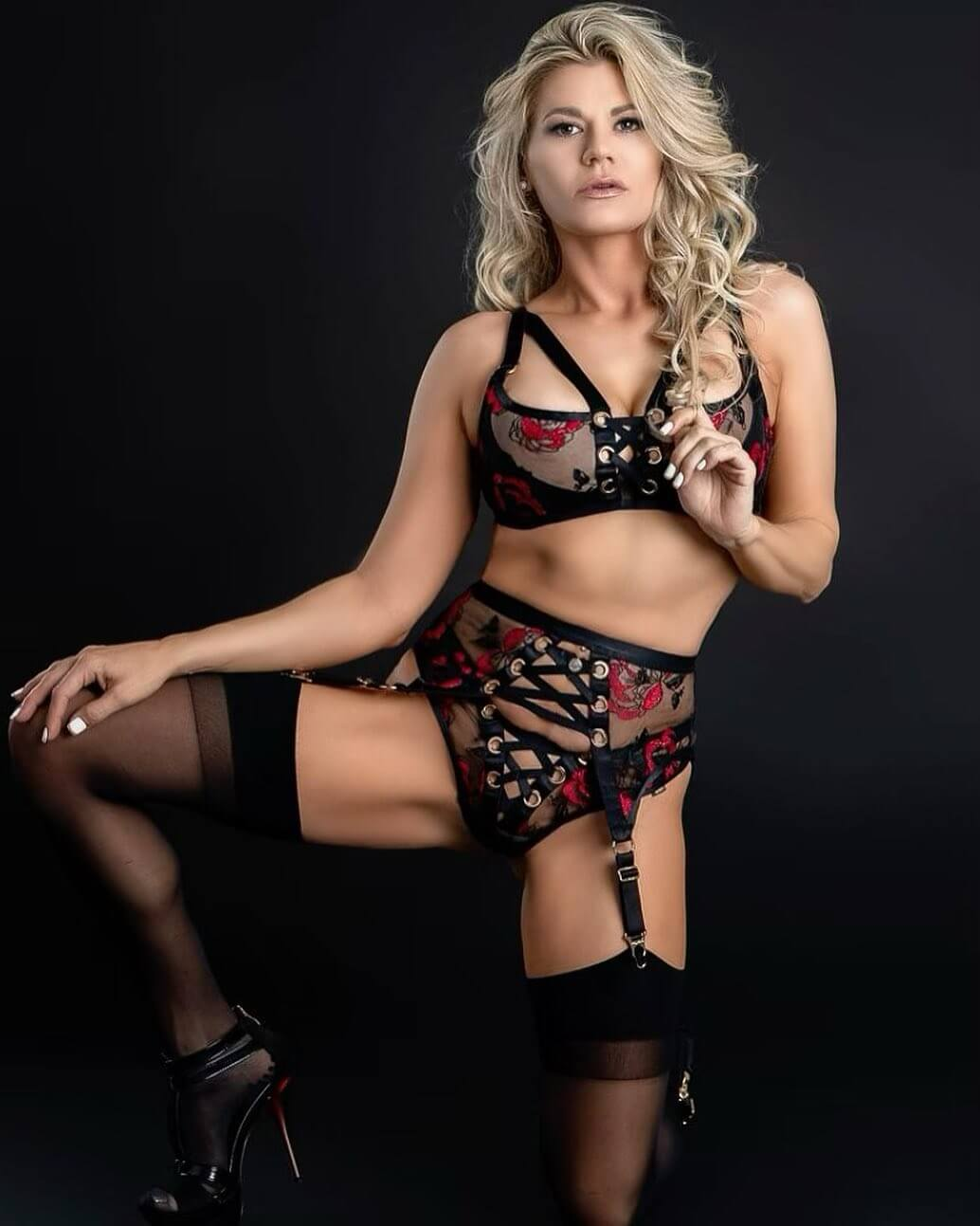 Beautiful smiling Texas blonde model Linzy Austin @tx_girl_next_door wearing black lingerie with black nylon stockings and high heels kneeled holding one leg up showing her hot body and banties