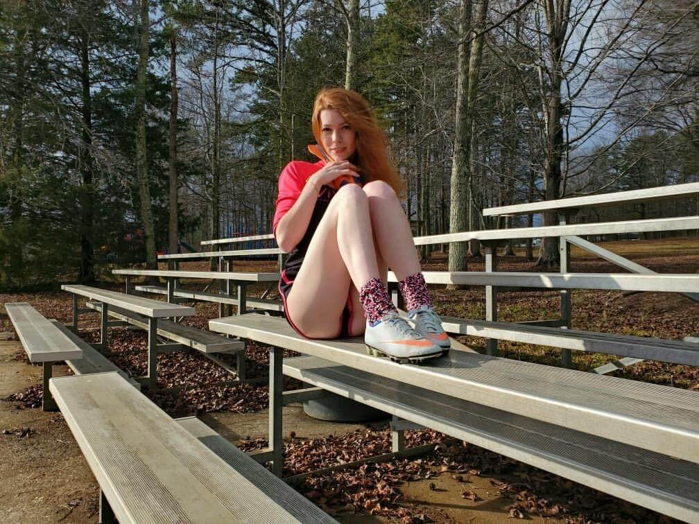 Beautiful young redhead American model Starfire @ starfirelove18 wearing sport shorts and sneakers sitting on the bleachers with her legs folded