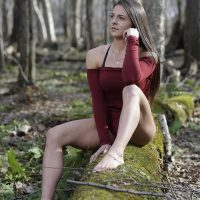 Beautiful Canadian model bare feet in the woods wearing a red top and short red shorts