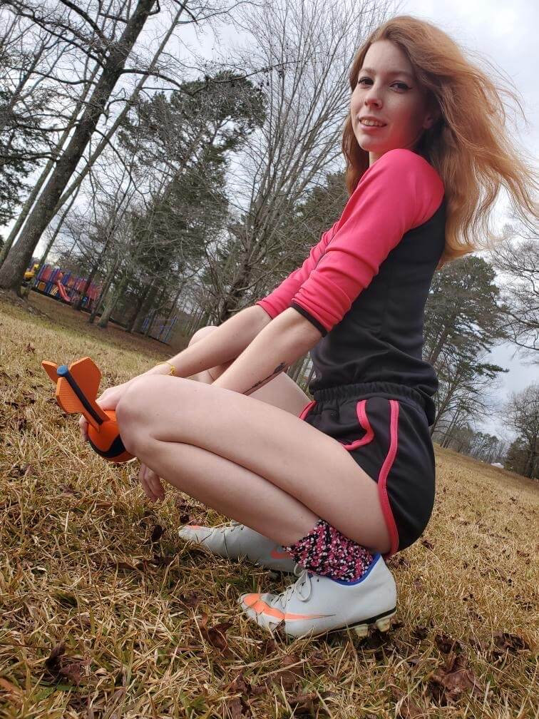 Beautiful young redhead American model Starfire @ starfirelove18 crouching on the lawn wearing sport shorts and sneakers showing her slim sexy bare legs in a fun sexy photo session on the field