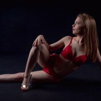Beautiful young model wearing red lingerie and high heels in a boudoir photo session