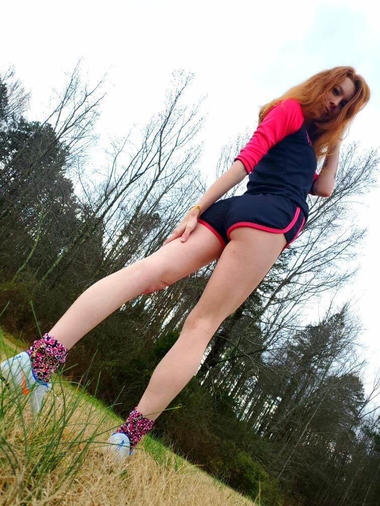 Beautiful young redhead American model Starfire @ starfirelove18 standing on the lawn wearing sport shorts and sneakers showing her slim sexy bare legs and tight booty in a fun sexy photo session on the field