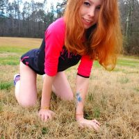 Beautiful young redhead model wearing sport shorts and sneakers in a fun sexy photo session on the field