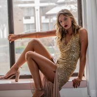 Beautiful blonde New York model Kelsey Joan O'Reilly @kelseyjoanoreilly wearing an open golden dress showing her long sexy legs and bare feet sitting by a window. Photo by Ken Grille Fashion Photography @kengrillefashionphotography
