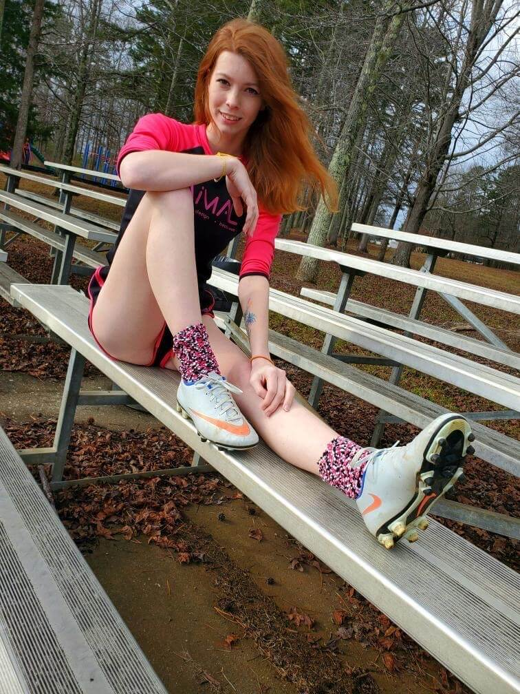 Beautiful young redhead American model Starfire @ starfirelove18 sitting on the bleachers wearing sport shorts and sneakers showing her sexy bare legs in a fun sexy photo session on the field