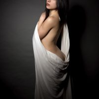 Beautiful Italian model Cloty looking over her shoulder draped in a white sheet for a boudoir photo session