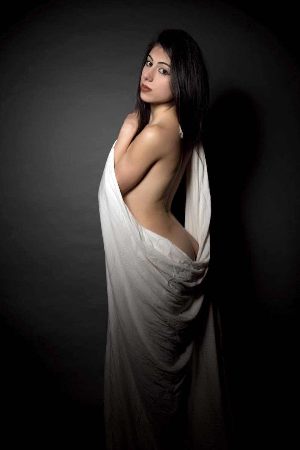 Beautiful Italian model Cloty @__cloty__ looking over her shoulder draped in a white sheet revealing her booty for a boudoir photo session