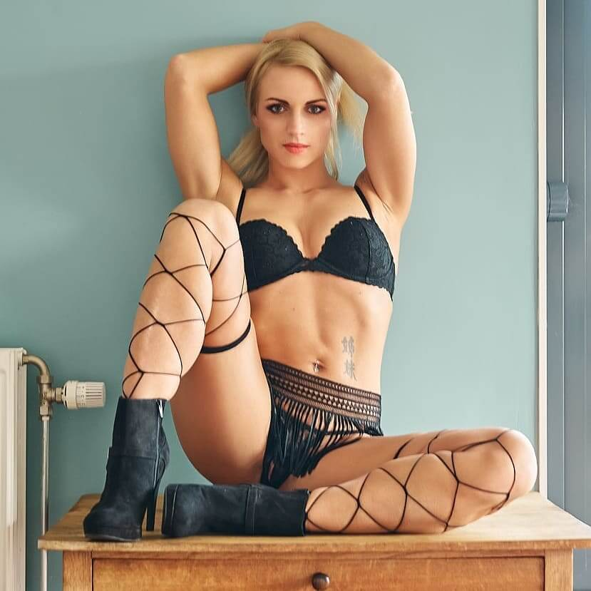Willeke Bartels @willekebartels.fitmodel sitting on a table with her arms up and sexy legs open wearing black lingerie showing some hot cleavage in a boudoir photo session