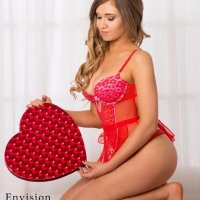 Beautiful Canadian model Amber Mardynalka kneeled bare foot on the floor wearing special pink lingerie holding a big red heart shaped chocolate boy in a sexy valentine's day photo session
