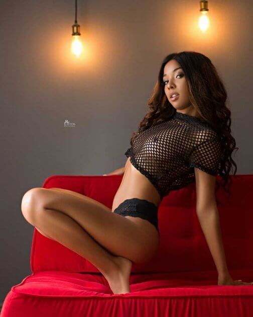 Beautiful brunette model Aurora the Princess @auroratheprincess braless wearing a black fishnet top with black lingerie bare foot showing some boobs in a sexy photo session by RW Llister photography @rwlisterphotography2