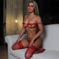 Russian blonde Playboy model Tatiana Brovkina @brovkina_model showing some sexy boobs wearing red lingerie kneeled on a white sofa